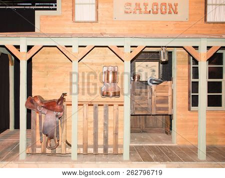Saloon Facade In The Farwest American With A Saddle Of Horse Resting On The Ruff