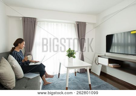 Happy Excited Asian Female Freelancer Working In Hotel Room: She Sitting On Comfortable Sofa With Pi