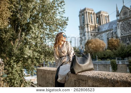 Young Woman Tourist Sitting Near The Famous Notre Dame Cathedral During The Morning Light Traveling