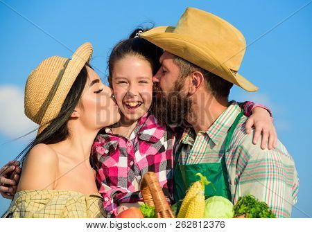 Family Farm Concept. Parents And Daughter Farmers Celebrate Harvest Holiday. Family Farmers Hug Kiss