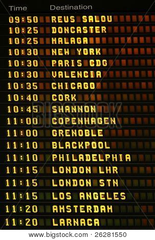 An electronic airport airplane departures board with times and destinations.
