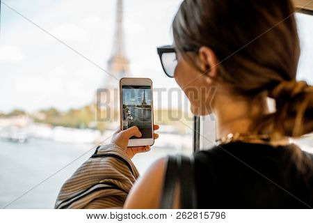 Young Woman Photographing With Smartphone Eiffel Tower From The Subway Train In Paris. Image Focused
