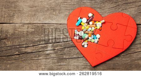 Heart Puzzle Red And Colored Pills And Capsules On Wood Background. Concept Treatment Of Heart Disea