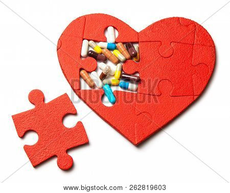 Heart Puzzle Red And Colored Pills And Capsules Isolated On White Background. Concept Treatment Of H