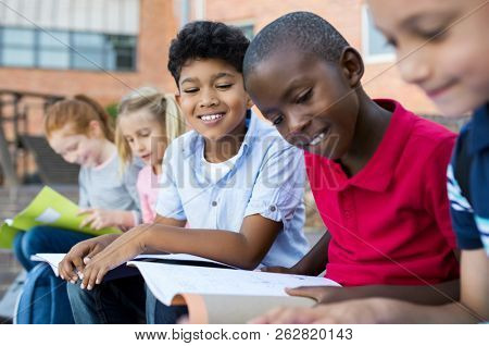Multiethnic children sitting in a row and reading from notebook all together. School kids revising notes for exams sitting on the steps outside the elementary school. School boy studying for classwork