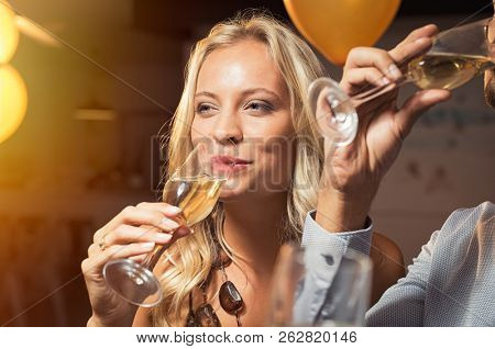 Young woman holding white wine glass and taking a sip. Closeup face of beautiful blond girl enjoying party at nightclub and drinking. Portrait of woman feeling good with sparkling glass of champagne.