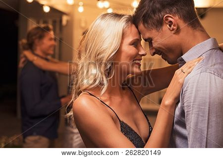 Beautiful loving couple dancing under the patio illuminated by wires of light bulbs. Young woman in love hugging her boyfriend. Romantic girl and elegant guy embracing outdoor at party night.