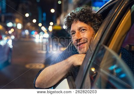 Smiling man looking outside from car window at night. Handsome business man enjoying taxi ride viewing the cityscape. Happy man traveling by taxi during vacation.