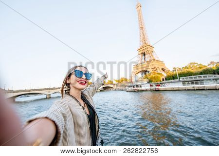 Young Woman Tourist Making Selfie Photo With Eiffel Tower On The Background From The Boat During The