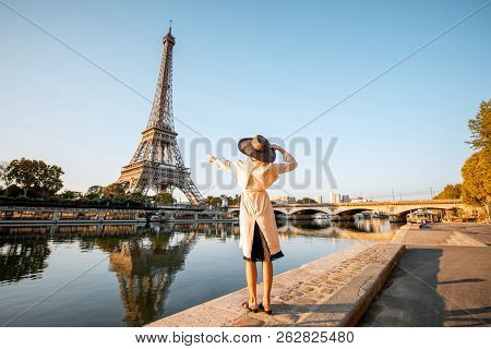 Young Woman Tourist Enjoying Landscape View On The Eiffel Tower With Beautiful Reflection On The Wat