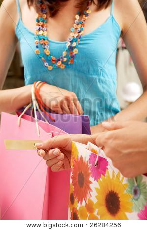 Close-up of woman?s hand holding credit card and bags with another female near by during shopping in the mall