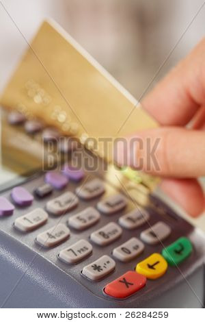 Close-up of payment machine buttons and human hand holding plastic card