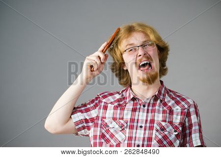 Bearded man having trouble with combing his hair using brush. Male haircare problems concept. poster