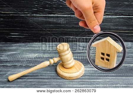 Wooden House And A Hammer Of The Judge On A Black Background. Court Cases On Property And Real Estat