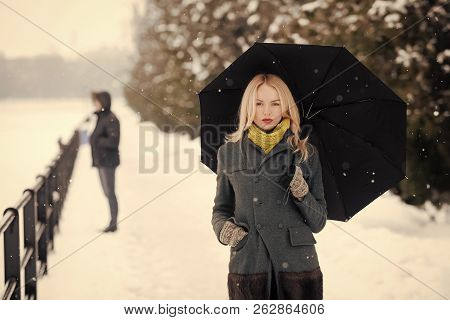 Woman With Long Blond Hair On White Snow Landscape. Model In Grey Coat, Scarf And Mittens. Holidays