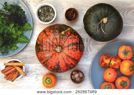 Green And Orange Pumpkin, Persimmons And Ingredients For Tasty Vegetarian Cooking On Light Wooden Su