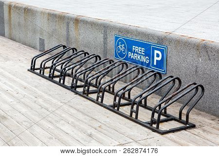 The Bicycle Parking From Metal Of Black Color On A Wooden Flooring For Safe Fixing Of Wheel Vehicles