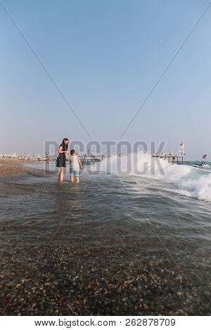 Mom And Son Walking On The Beach. Sea Horizon And Blue Sky. Family Vacation At Sea. Summer Time Sea