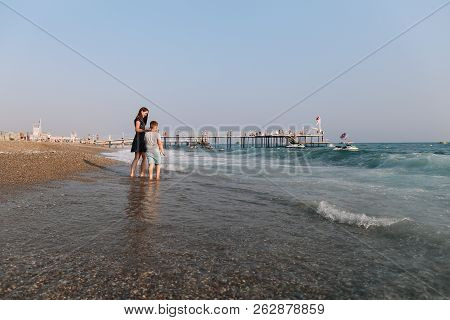 Mom And Son Walking Along The Beach. Sea Horizon And Blue Sky. Family Vacation At Sea. Summer Time S