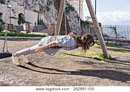 Joyful, Beautiful Hipster Girl In Casual Look And Windy Hair, Fooling Around On Swing Planking, Dead