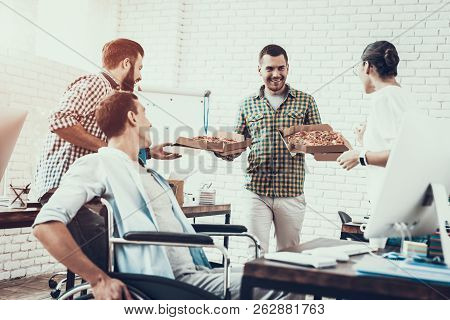 Young People Have Lunch With Pizza In Office. Teamwork In Office. Young Worker. Sitting Man. Box Wit