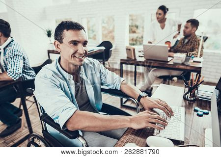 Man On Wheelchair Working On Computer In Office. Disabled Young Man. Man On Wheelchair. Recovery And