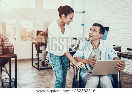Woman Near Man On Wheelchair With Tablet In Office. Smiling Woman. Disabled Young Man. Man On Wheelc