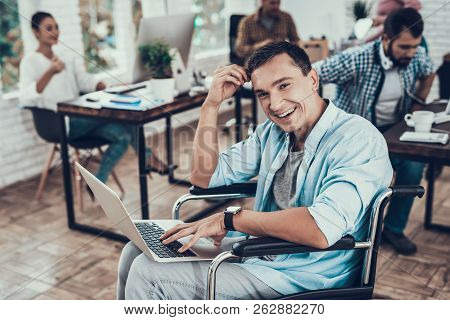 Disabled Man On Wheelchair With Laptop In Office. Disabled Young Man. Man On Wheelchair. Recovery An