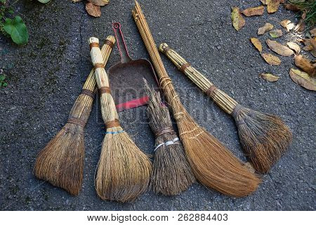 Brown Brooms And A Red Scoop On Gray Asphalt With Dry Fallen Leaves