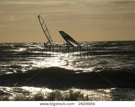 Two Windsurfers At The Ocean; One Down