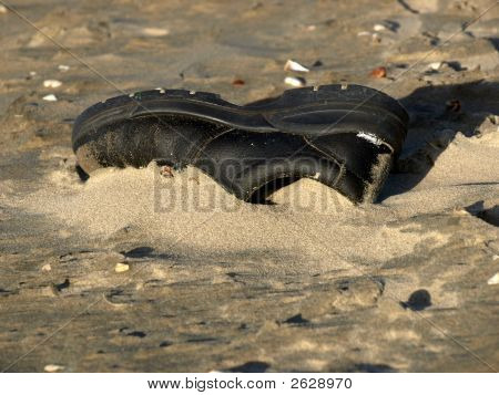 One Loney Black Shoe In The Sand