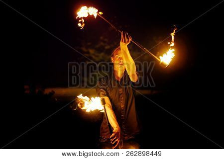 Fire Show. The Fakir Juggles With Two Staff. Night Performance. Dramatic Portrait. Fire And Smoke
