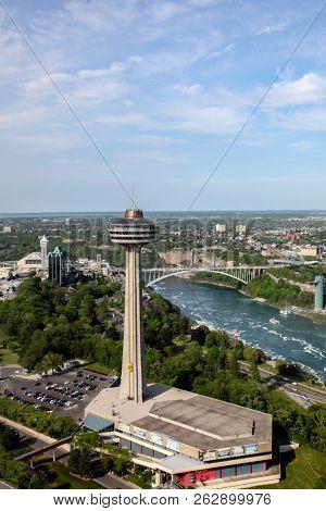 NIAGARA FALLS, ONTARIO, CANADA - MAY 27, 2016:  Niagara Falls with a view of the Americans side from Ontario, Canada with Skylon Tower seen in Niagara Falls on May  27, 2016.