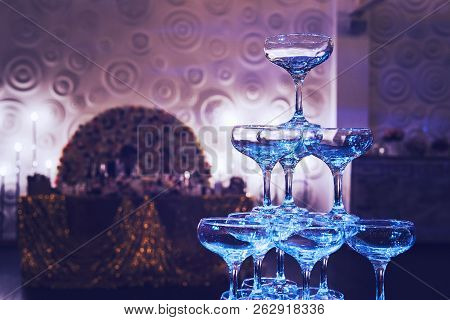 Awesome shot of glittering 3-tier champagne tower at the decorated banquet hall background. Beautifull built-in set of coupe glasses at a wedding room. Wedding champagne tower is ready for pouring. poster