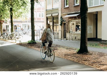 Germany, Muenster, October 5, 2018: A Woman Rides A Bike Along A Cycle Path. Everyday City Life.