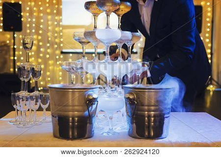 Man in suit fills the 4-tier champagne tower with sparkling wine at the illuminated banquet hall background. The glasses tower with champagne is on a table at festive occasion background. Cascade poster