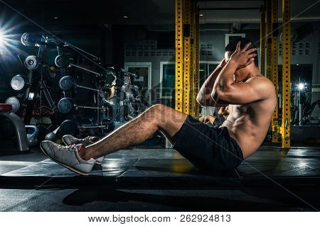 Muscular Guy Doing Sit Ups At Gym With Other People In Background. Young Athlete Doing Stomach Worko