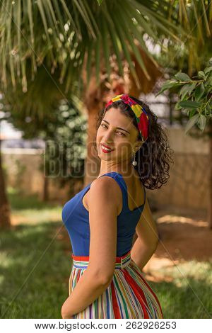 Colorful Portrait Of Young Smilng Brunette Wearing Blue Sleeveless Top, Striped Skirt And Red And Ye