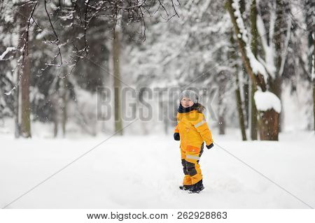 Cute Little Boy In Yellow Winter Clothes Walks In During A Snowfall. Outdoors Winter Activities For