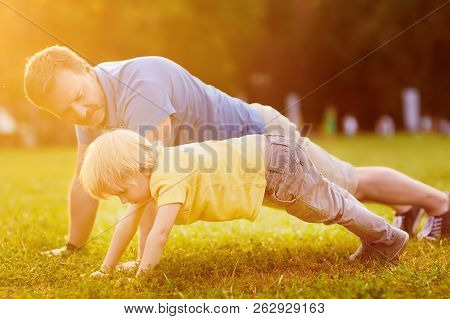 Little Boy And His Father Doing Plank Exercise In Sunny Summer Park. Outdoor Sport Activities For Fa