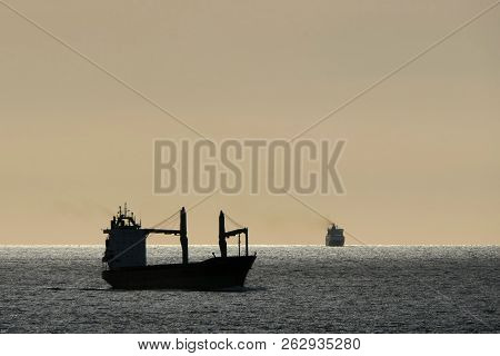 Ships On The Way In The Evening. A Cargo Ship And Container Ship Travel On The High Seas. The Sky Is