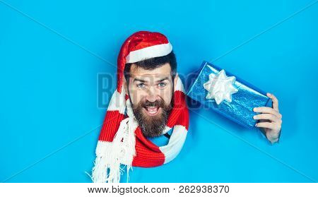 Bearded Man In Santa Hat And Scarf Holds Presents Gift Box Through Paper Hole. Santa Claus With Gift