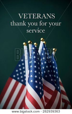 some american flags and the text veterans thank you for your service against a dark green background