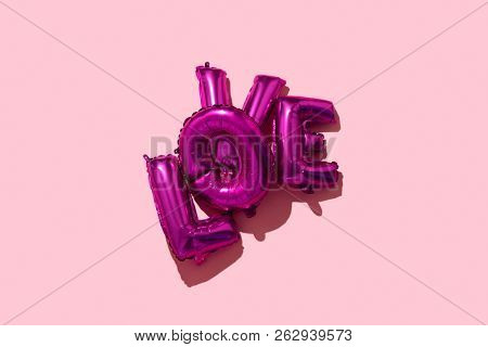 some fuchsia letter-shaped balloons forming the wor love on a pink background, with some blank space around them