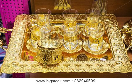 Oriental, Turkish, Arabic gilded tea set, glasses on a tray on a shop window poster