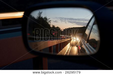 Heavy traffic reflecting in the mirror by night