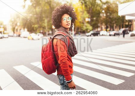 A Young African American Man With A Red Backpack Crosses The Road At A Pedestrian Crossing In The Ci