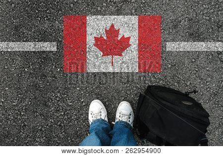 A Man With A Shoes And Backpack Is Standing On Asphalt Next To Flag Of Canada And Border