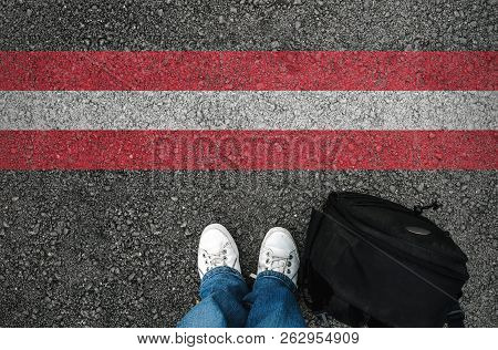 A Man With A Shoes And Backpack Is Standing On Asphalt Next To Austrian Flag And Border