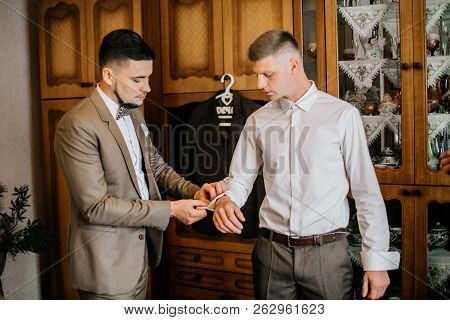 Stylish Groomsmen Helping Happy Groom Getting Ready In The Morning For Wedding Ceremony. Luxury Man